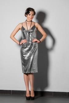 Model in retrostijl zilveren klatergoudjurk met pluim in haar