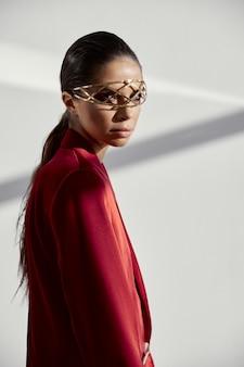 Model in rode blazer met versiering op het gezicht