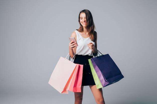 Model in schoenen met hoge hakken houdt verschillende papieren boodschappentassen geïsoleerd op wit
