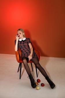 Model in stijlvolle herfstkleding in een modestudio met rode appels. poster. winkelen