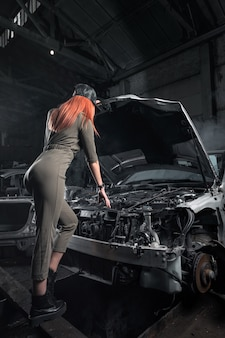 Model in stijlvolle kleding staande tegen op open motorkap in gedemonteerde auto in de garage.
