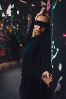Model in zwart, ogen bedekt met zwart lint