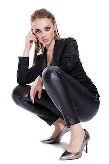 Model in zwarte jas en leren broek op een witte achtergrond gestyled achterhaar