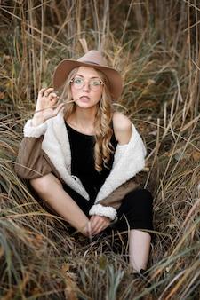 Model in zwarte jurk in droog gras