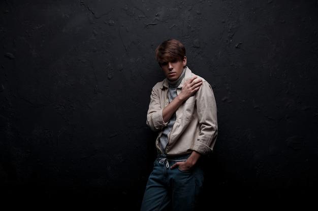 Model jonge man in een lichte stijlvolle lente jas in een trendy gebreide grijze golf met een modieus kapsel in vintage spijkerbroek poseren binnenshuis in de buurt van de zwarte muur. herenkleding in amerikaanse stijl