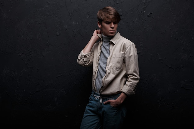 Model jonge man in een modieuze lente lichte jas in een vintage grijze trui in spijkerbroek met een modieus kapsel poseren in een kamer in de buurt van de zwarte muur. stijlvolle geweldige kerel. amerikaanse stijl