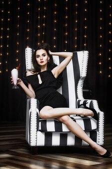 Model jonge vrouw mooi en luxueus zittend in een zwart-wit gestreepte stoel modieus en stijlvol