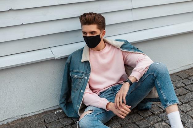 Model jongeman in stijlvol spijkerjack in gescheurde modieuze spijkerbroek in trendy zwart masker zit op stenen tegels in de buurt van vintage muur in de stad. knappe jongen in mode casual kleding op straat buitenshuis.