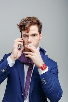 Model knappe man in een pak met een sigaret en praten aan de telefoon