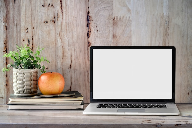 Model laptop met boek, appel en kamerplant op houten tafel.