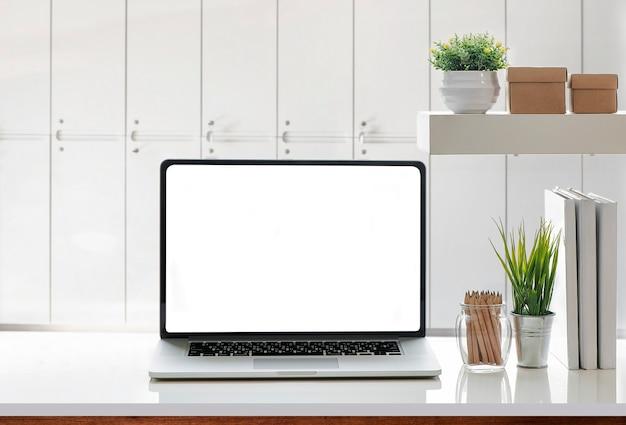 Model laptop met wit scherm en benodigdheden op witte tafel.