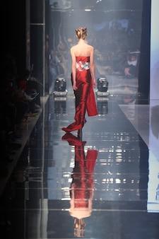 Model lopen terug op spiegel runway fashion show catwalk met reflectie op de vloer