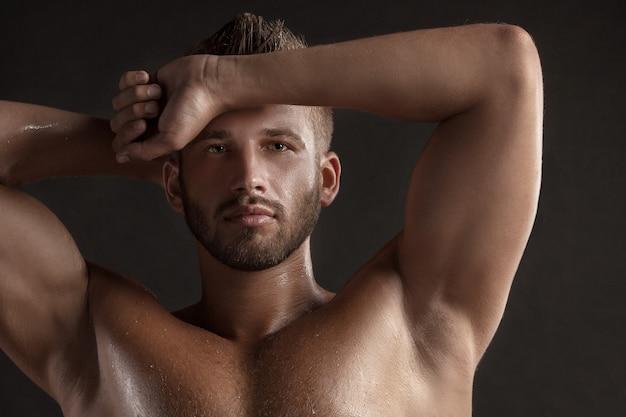 Model man met een open bovenlijf op een donkere achtergrond, gespierd lichaam van een jonge man in spijkerbroek. geschoten in een studio.