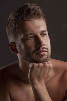 Model man met een open bovenlijf op een donkere achtergrond, gespierd lichaam van een jonge man in spijkerbroek