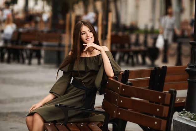 Model meisje in een jurk zit op de bruine bank in de stad op een zonnige zomerdag. buitenshuis lifestyle mode portret.