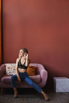 Model meisje in jeans en kanten zwarte beha poseren in het interieur