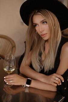 Model meisje in met zachte make-up en blond haar genieten van wijn aan de tafel van het café in de zomeravond.