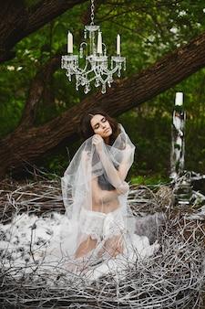 Model meisje met slank lichaam in modieuze kanten lingerie en de sluier zit in het enorme nest in het groene mystieke bos