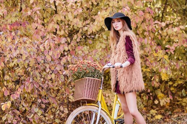 Model met een fiets in herfstwandelingen in het park