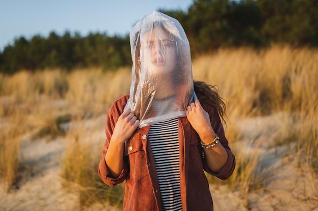 Model met een plastic zak op haar gezicht, met de nadruk op milieuproblemen