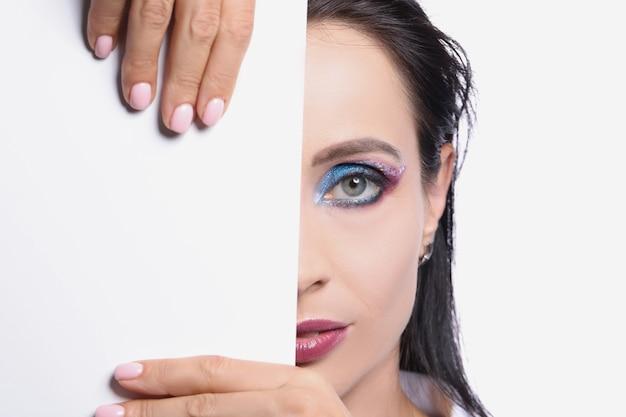 Model met gekleurde oogmake-up perfecte halve gezichtshuid met modieuze witte kaartsjabloon