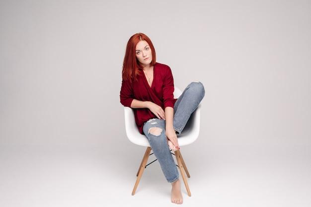Model met gemberhaarzitting op witte stoel