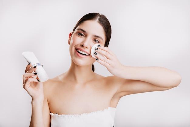 Model met groene ogen met op witte muur. brunette hydrateert het gezicht met dove-crème.