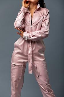 Model met lang donkerbruin haar, trendy roze jumpsuit poseren.