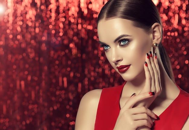 Model met make-up en manicure in een rode en zwarte kleuren