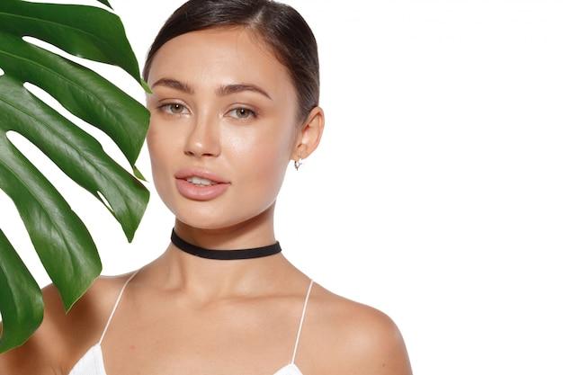Model met natuurlijke make-up en groene blad geïsoleerd. spa en wellness.