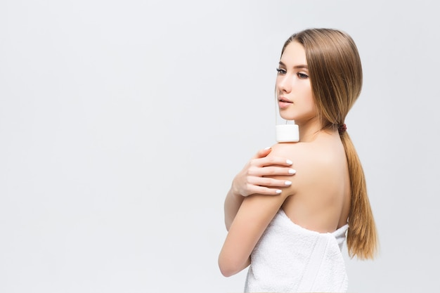 Model met natuurlijke make-up met crème op haar schouders