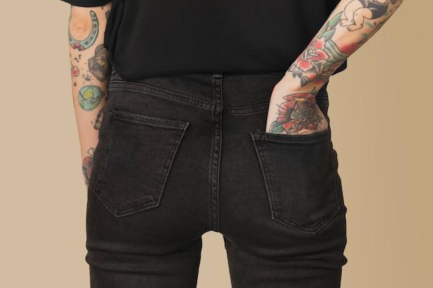 Model met tatoeage in zwart t-shirt en spijkerbroek