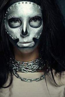 Model met zilveren maskerschedelverf op donkere achtergrond