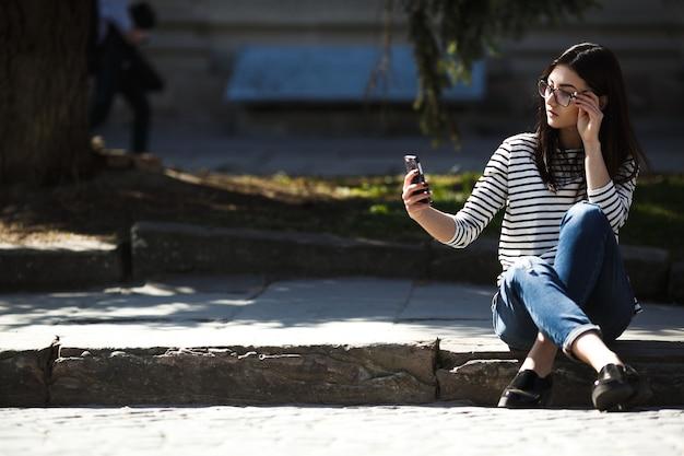 Model midden in de stad met telefoon