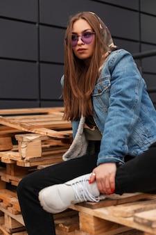 Model modieuze jonge vrouw hipster in trendy casual denim kleding in stijlvolle violet bril poseert buiten in de stad. trendy sexy glamoureuze meisje mannequin zit op houten pallets in de straat