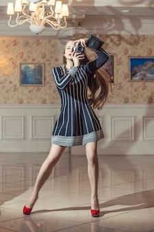 Model mooie vrouw in modieuze kleding te midden van luxe vintage retro interieur