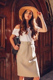 Model. openluchtportret van jonge mooie vrouw die strohoed draagt en rugzak houdt.
