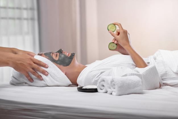 Model poseren met een kleimasker op haar gezicht liggend op een bed