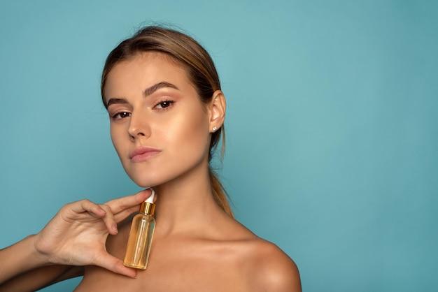 Model poseren met gloeiende huid met een glazen fles cosmetica op blauwe achtergrond