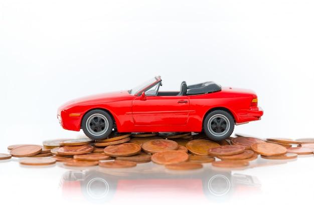 Model rood parkeerterrein op stapel gouden die muntstukken op witte achtergrond worden geïsoleerd.