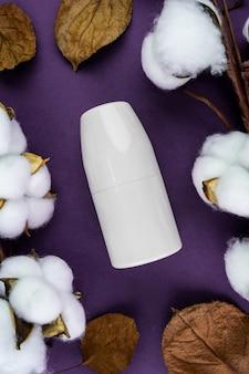 Model transpiratiewerend middel op een paarse achtergrond. katoen en bladeren zijn natuurlijke cosmetica.