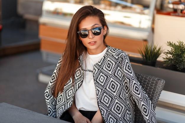 Model van de mooie jonge stijlvolle vrouw in een trendy jasje met zonnebril zit in een restaurant op straat