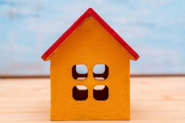 Model van een houten geel huis met een rood dak. verhuur en verkoop van gebouwen en huisjes.