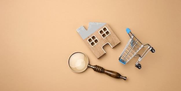 Model van een houten huis, een miniatuur winkelwagentje en een vergrootglas op een lichtbruine achtergrond. huiszoekconcept voor huur, aankoop, hypotheek