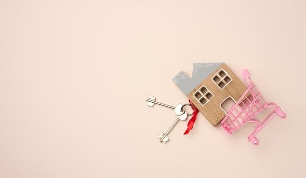 Model van een houten huis, een miniatuur winkelwagentje op een beige achtergrond. aankoop onroerend goed, hypotheek