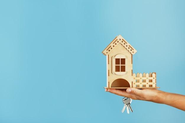 Model van een houten huis in de palm van je hand met sleutels op een blauwe achtergrond.