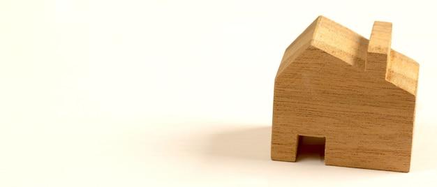 Model van een houten huis op een witte achtergrond voor het plannen van het kopen en verkopen van een huis.