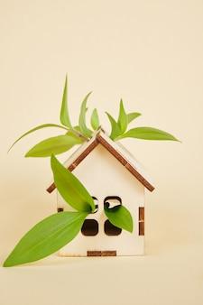 Model van een huis op een beige achtergrond, eco huis concept, bladeren en speelgoed huis kopie ruimte