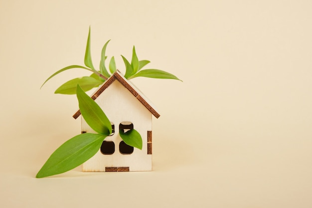 Model van een huis op een beige achtergrond, eco-huisconcept, groene bladeren en een exemplaarruimte van het speelgoedhuis
