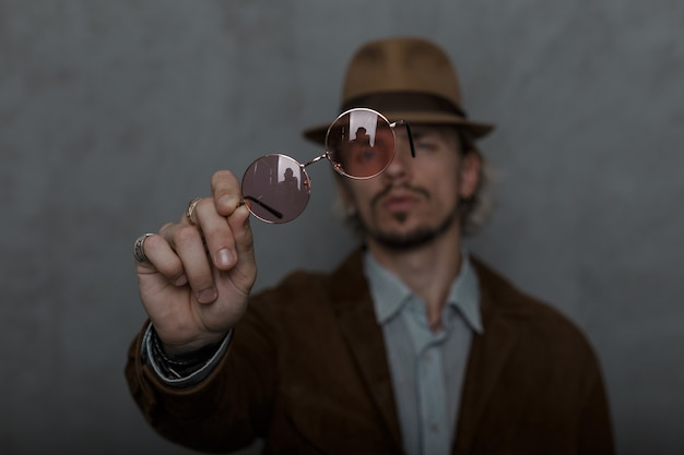 Model van een jonge man in elegante kleding in retro stijl in een ouderwetse elegante hoed staat en houdt vintage bril naar de camera binnenshuis. coole knappe jongen. focus op een bril.